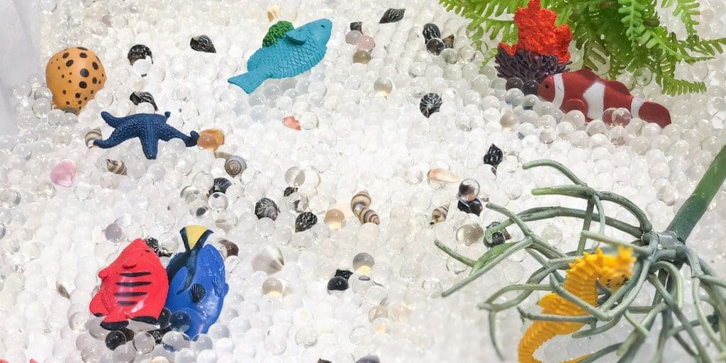 sensory bin with water beads, seahorse and fish