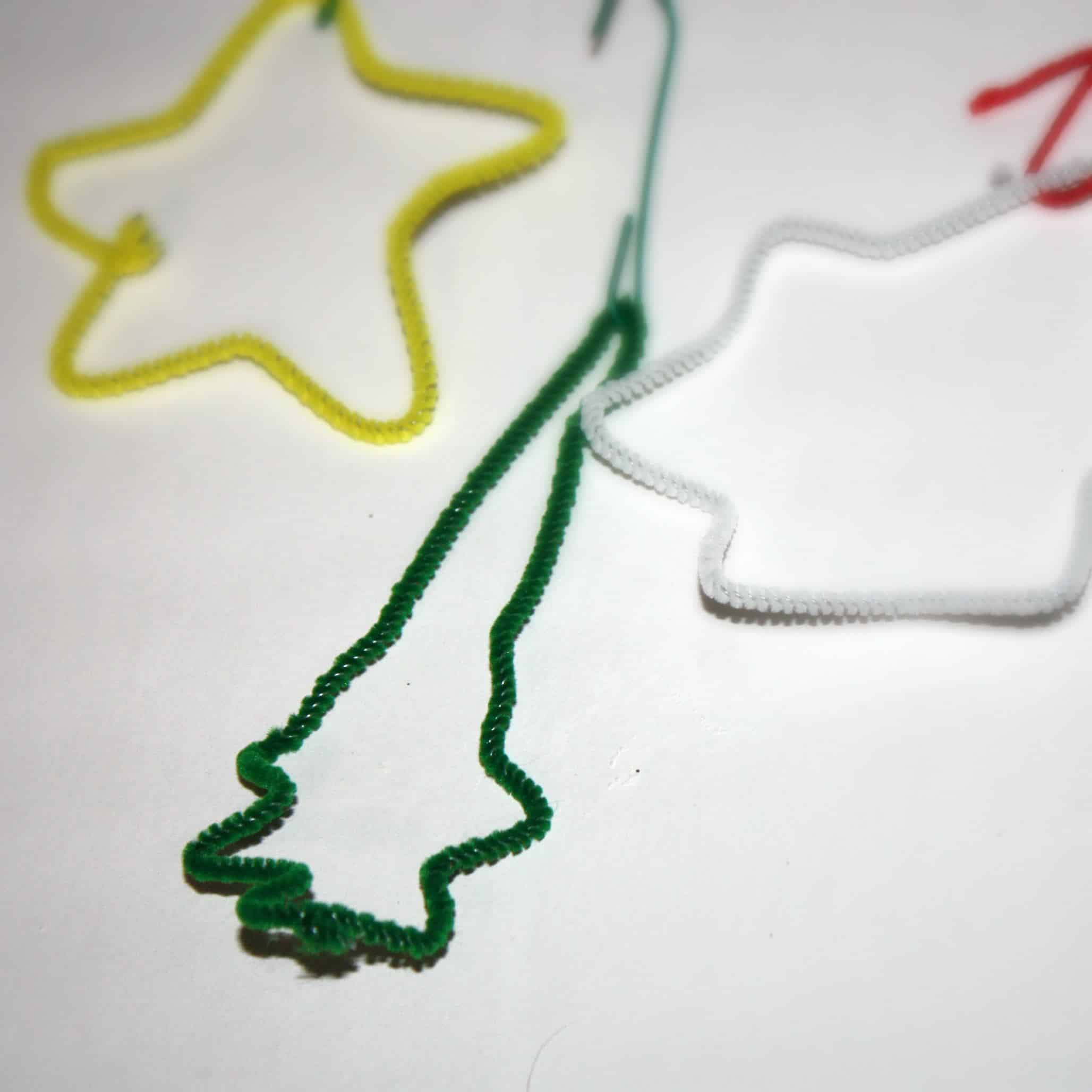 These kid made ornaments are made out of pipe cleaners wrapped around cookie cutters! So simple and easy for kids to make on their own!
