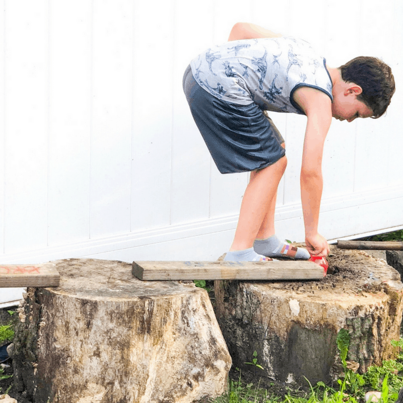 boy balancing on tree trunks backyard game treasure hunt